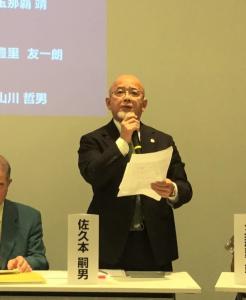 沖縄県主催の会合であいさつする佐久本嗣男さん